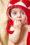 Baby in red bonnet. Blue eyed baby in red bonnet Stock Photo