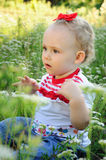 Baby with red bow on the meadow Stock Image