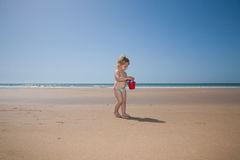 Baby with red bucket at beach Stock Photo