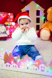Baby in red cap sit on background of a garland of lights, teddy bears and toy houses and plays Stock Photos