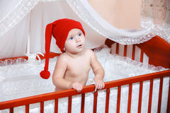 Baby in red cap smiling in bed Royalty Free Stock Photos