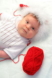 Baby in red Christmas hat with a red clew Stock Photo