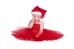 Baby with red dress. Baby sitting in red dress and red christmas hat on head Royalty Free Stock Images