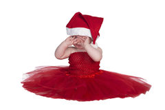 Baby with red dress. Baby sitting in red dress and red christmas hat on head Stock Photography