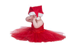 Baby with red dress. Baby sitting in red dress and red christmas hat on head Royalty Free Stock Photography