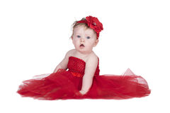 Baby with red dress. Baby sitting in red dress and red flower on head Stock Images