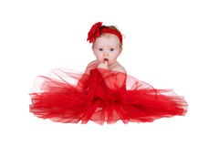 Baby with red dress. Baby sitting in red dress and red flower on head Royalty Free Stock Photography