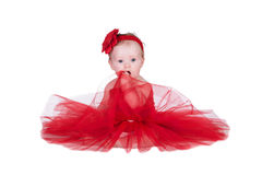 Baby with red dress. Baby sitting in red dress and red flower on head Stock Photo