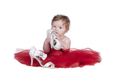 Baby with red dress. Baby sitting in red dress playing with white shoes Stock Photos