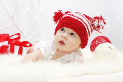 Baby in red hat with gifts. Lovely baby in red hat age of 3 months with gifts Royalty Free Stock Photo