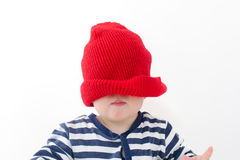 Baby in a red hat pulled over his face studio Stock Image