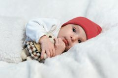 Baby in red hat shows tongue Stock Photo