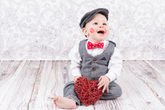 Baby with red kiss and heart. Lovely baby boy in barret with lipstick kiss on his cheek and red heart Stock Photography