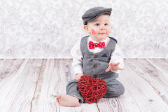 Baby with red kiss and heart. Lovely baby boy in barret with lipstick kiss on his cheek and red heart Stock Photos