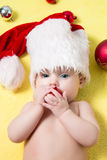 Baby in a red Santa hat with balls on the New year tree. Beautiful little  celebrates Christmas Stock Images