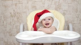 Baby in red Santa hat laughs and smiles while sitting in high chair. Christmas. New Year.  stock footage