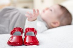 Baby red shoes and babe lying on the background Stock Image