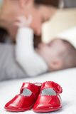 Baby red shoes pair and babe on the background Royalty Free Stock Photography