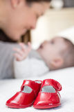 Baby red shoes pair and babe on the background Royalty Free Stock Photos