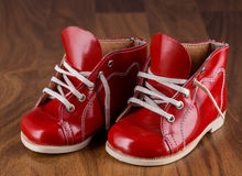 Baby red shoes on a wooden floor. Female (baby) red shoes on a wooden background Royalty Free Stock Photo