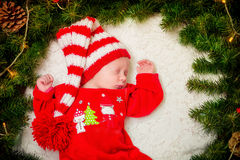 Baby in a red suit Santa in a Christmas wreath Royalty Free Stock Photo