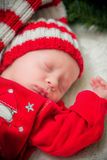 Baby in a red suit Santa in a Christmas wreath Stock Image