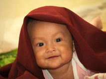 Baby in Red Veil. Happy face asian smilling baby in red veil royalty free stock image