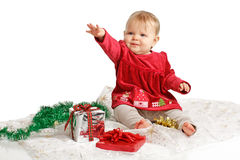 Baby in red velvet Christmas dress reaches up Stock Photo