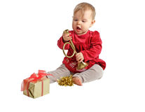 Baby in red velvet dress inspects toy horn Royalty Free Stock Photo