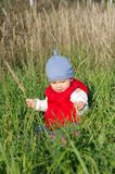 Baby  in red waistcoat sitting on grass outdoors. Baby age of 11 months in red waistcoat sitting on grass outdoors Stock Image