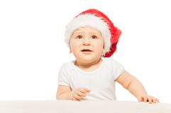 Baby in red Xmas hat looks up on white background Royalty Free Stock Photos