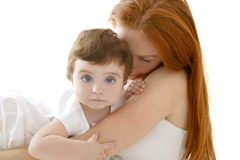 Baby and redhead mother hug on white Stock Images