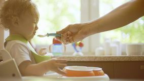 Little baby girl refuses to eat off spoon stock images