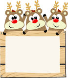 Baby reindeers with wooden sign board Stock Photos