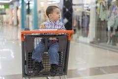 Baby reitet in eine Laufkatze durch ein Einkaufszentrum stockbild