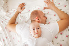 Baby relaxing on his father's back Stock Images