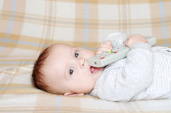 Baby with remote control Royalty Free Stock Photography