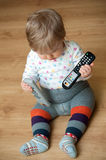 Baby with remote controls Stock Photography
