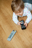 Baby with remote controls. Baby girl laying on the floor playing with the TV remote controls Stock Photos