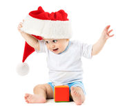 Baby removes his santa hat Stock Image