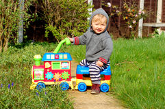 Baby on ride on train. Todler playing with his ride on train in the garden Royalty Free Stock Images