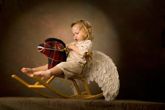 Baby rides a woody horse Royalty Free Stock Photo