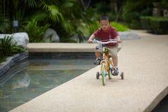 Baby riding bicycle Stock Photos
