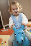 Baby riding a toy horse Royalty Free Stock Image