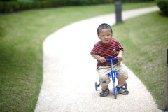 Baby riding tricycle Royalty Free Stock Photos