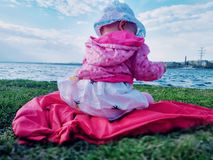 Baby on the river Bank. The baby sits on the Bank of the river and plays. The view from the back. Unusual perspective royalty free stock photo