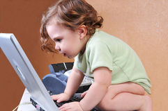 Baby riveted to the laptop screen Royalty Free Stock Photos