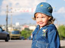 Baby on a road. Little girl is standing close to the road with heavy traffic. Parents be careful Royalty Free Stock Photo