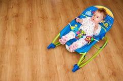 Baby in rocker. Cute baby girl in rocker on laminate floor stock image