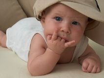 Baby-rocker. Baby in the big cap and two fingers in a mouth Stock Image